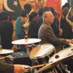 cool japanese jazz pianist behind a massive pakistani painting